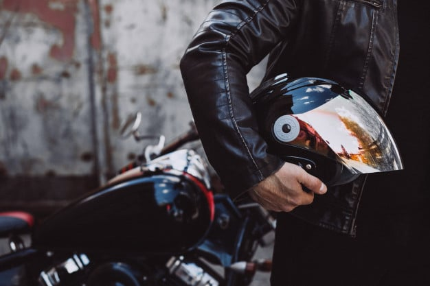 homme tenant un casque de moto