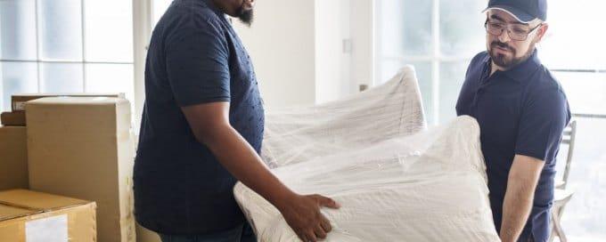 Déménageur qui porte un meuble