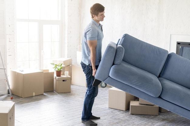 homme portant un canapé