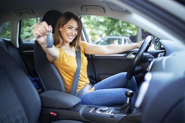 jeune femme qui tend une paire de clé dans une voiture